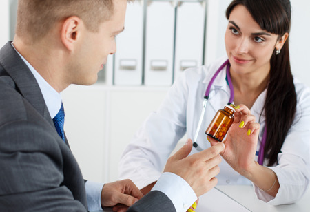 pharmacologist: Beautiful female medicine doctor giving to male patient in business suit jar of pills. Antidepressant or man sexual potency cure. Medical and pharmacy concept. Businessman visiting therapeutist