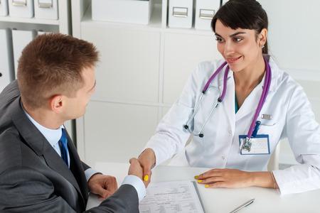 dando la mano: Hermosa sonriente médico medicina femenina dando la mano con el paciente masculino. Asociación, la confianza y la ética médica concepto. Apretón de manos con el cliente satisfecho. Apretón de manos Agradecido por tratamiento excelente Foto de archivo
