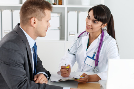 Beautiful smiling female medicine doctor communicating with male patient in business suit and filling medical form. Healthcare or insurance concept. Physician ready to examine patient and help