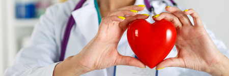 Female medicine doctor's hands holding red toy heart in front of her chest closeup. Letterbox view. Medical help, prophylaxis or insurance concept. Cardiology care,health, protection and prevention Standard-Bild