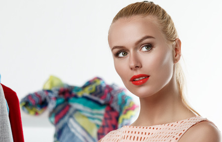 brand new: Thoughtful beautiful blonde woman standing near wardrobe rack full of clothes and choosing dress. Shopping and consumerism or stylist concept. Nothing to wear and hard to decide concept