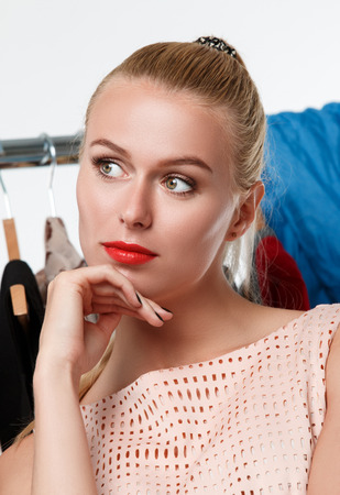 Beautiful blonde woman suffering near wardrobe rack full of clothes choosing dress to wear. Nothing to wear, hard to decide or stylist concept Stock Photo
