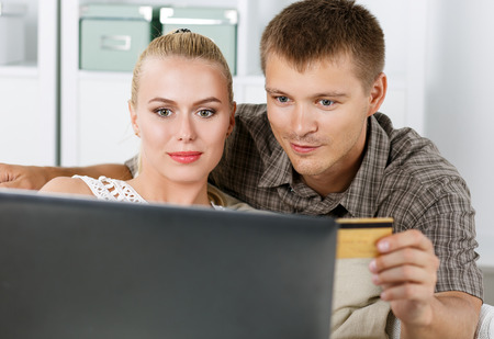 house shopping: Family couple making shopping over internet looking in notebook and paying with credit card. Husband and wife buying new stuff in house. Shopping, consumerism, delivery and present concept