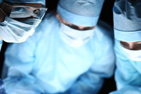 emergencia: Grupo de cirujanos en el trabajo que operan en quirófano. Reanimación equipo de medicina ahorro paciente. Doctor llevaba máscara protectora mirando a puerta cerrada. Cirugía y el concepto de emergencia Foto de archivo