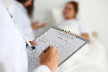 historia clinica: Mujer médico de medicina rellenando lista del historial médico del paciente durante todo el barrio. La atención médica o concepto de seguro. Physician listo para examina al paciente y ayudar