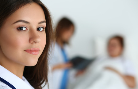 medical practice: Beautiful female medicine doctor looking in camera in front of patient lying in bed and communicating with traumatologist. Radiology or traumatology medical concept. Medical care or insurance concept