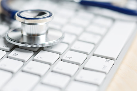 information technology: Stethoscope head lying on silver keyboard closeup. Medical concept. Modern medicine and high tech equipment concept Stock Photo