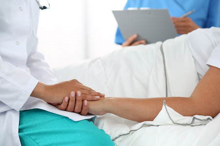 Friendly female doctors hands holding patients hand lying in bed for encouragement, empathy, cheering and support while medical examination. Trust and ethics concept. Bad news lessening and support Stock Photo