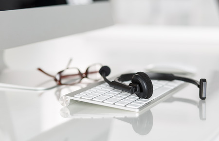 Call center service operator's empty working place. Headset, glasses, keyboard and monitor at helpdesk employee workplace. Effective and efficient business information, help and support concept