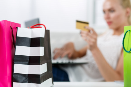 retail: Blond woman making purchasing via internet paying credit card. Focus on fresh buyings packed in colored paper bags standing in front of her. Shopping, consumerism, delivery and present concept