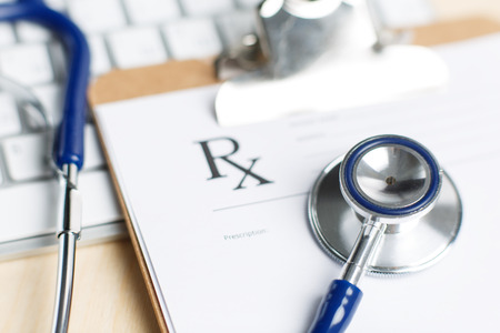 pharmacologist: Prescription form clipped to pad lying on table with keyboard and stethoscope. Medicine or pharmacy concept. Empty medical form ready to be used