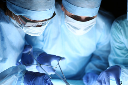 operating theater: Group of surgeons at work operating in surgical theatre. Resuscitation medicine team wearing protective masks holding steel medical tools saving patient. Surgery and emergency concept Stock Photo