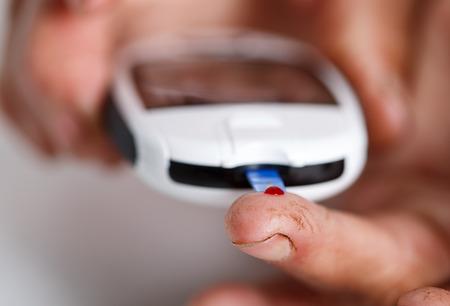 blood sugar level: Hands of elder diabetic woman measuring blood sugar with portable pocket glucometer. Medicine and healthcare concept. Stock Photo