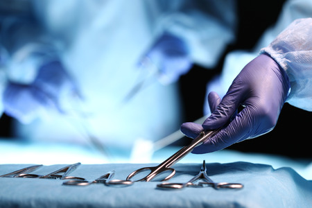 reanimować: Nurse hand taking surgical instrument for group of surgeons at background operating patient in surgical theatre. Steel medical instruments ready to be used. Surgery and emergency concept