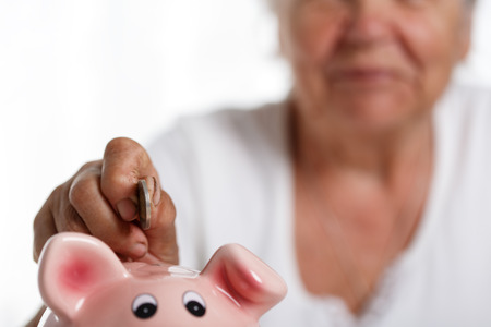 save: Elder woman putting pin money coins into pink piggybank slot. Budgeting expenses concept. Making savings and effective investment concept. Future needs deposit. Focus on coin. Retirement problems Stock Photo