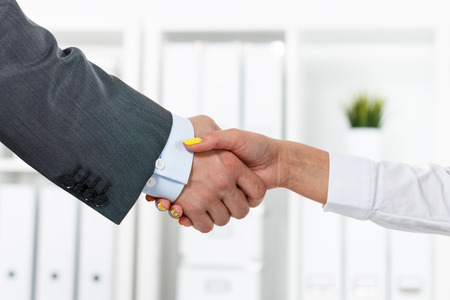 handclasp: Male and female handshake in office. Businessman in suit shaking womans hand. Serious business and partnership concept. Partners made deal, sealed with handclasp. Formal greeting gesture