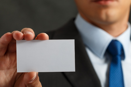 contact information: Businessman in suit and hand holding blank calling card. Male hand showing white visiting card in camera closeup. Partners contact information exchange concept. Introducing gesture at formal meeting Stock Photo