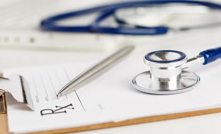 Forma de prescripción recortado a la almohadilla tendida en la mesa con el estetoscopio y pluma de plata. Medicina o el concepto de farmacia. Formulario médico vacío listo para ser utilizado
