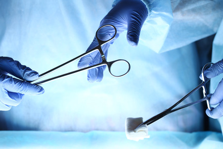 Cirujanos tomados de la mano y que pasan instrumento quirúrgico a otro médico durante el funcionamiento del paciente. Equipo de medicina de reanimación sosteniendo herramientas médicas de acero ahorro paciente. Cirugía y el concepto de emergencia