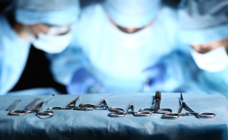 Surgical tools lying on table wile group of surgeons at background operating patient in surgical theatre. Steel medical instruments ready to be used. Surgery and emergency concept Banque d'images