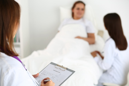 diagnosing: Female medicine doctor filling in patient medical history list during ward round. Medical care or insurance concept. Physician ready to examine patient and help