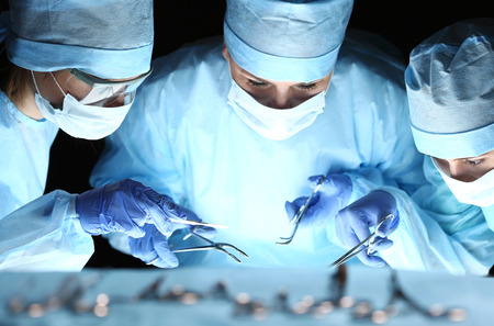 Group of surgeons at work operating in surgical theatre. Resuscitation medicine team wearing protective masks holding steel medical tools saving patient. Surgery and emergency concept Foto de archivo