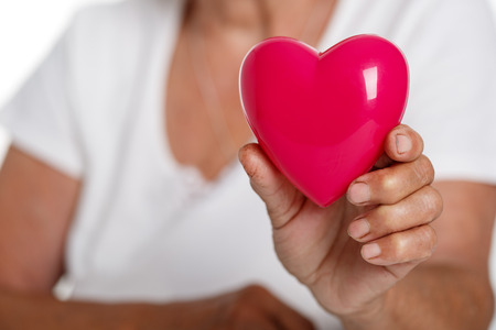 infarction: Elder woman holding red toy heart in front of her chest. Medical help, prophylaxis, insurance, surgery and resuscitation concept. Cardiology care,health, protection and prevention