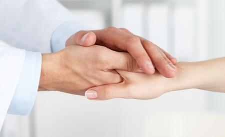 격려와 공감을위한 여성 환자의 손을 잡고 친절한 남자 의사의 손. 파트너십, 신뢰와 의료 윤리 개념. 나쁜 소식하게 약화 및 지원. 환자 응원 및