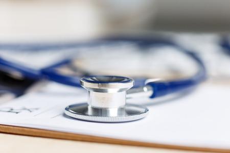 simbolo medicina: Forma de prescripción recortado a la almohadilla tendida en la mesa con el estetoscopio. Medicina o el concepto de farmacia. Formulario médico vacío listo para ser utilizado