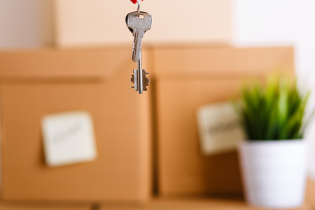 going places: Female hand holding keys over pile of brown cardboard boxes with house or office goods background. Moving to new place of living concept.