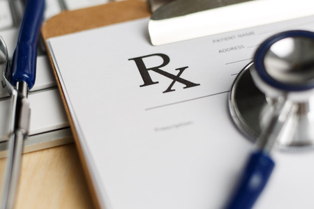 prescription pad: Prescription form clipped to pad lying on table with keyboard and stethoscope. Medicine or pharmacy concept. Empty medical form ready to be used