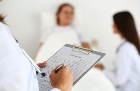 Mujer médico de medicina rellenando lista del historial médico del paciente durante todo el barrio, mientras que los pacientes comunicarse con el médico. La atención médica o concepto de seguro. Médico listo para examinar y ayudar a