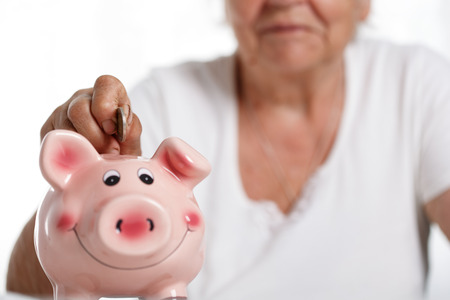 retirement nest egg: Elder woman putting pin money coins into pink piggybank slot. Budgeting expenses concept. Making savings and effective investment concept. Future needs deposit. Focus on coin. Retirement problems Stock Photo