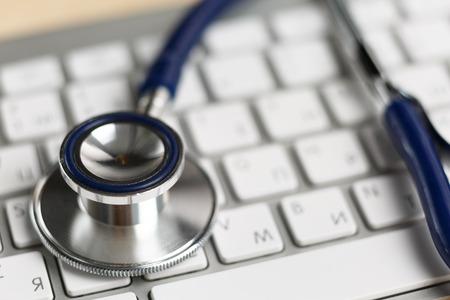 醫療保健: 聽診器頭趴在銀色鍵盤特寫。醫學概念。現代醫學和高科技裝備的概念 版權商用圖片