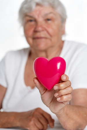 prophylaxis: Elder woman holding red toy heart in front of her chest. Medical help, prophylaxis, insurance, surgery and resuscitation concept. Cardiology care,health, protection and prevention. Healthy heart
