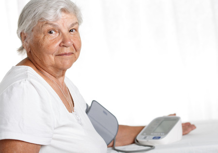 self exam: Elder woman measuring blood pressure with automatic manometer at home. Self health control, diagnosing and healthcare concept. Long and healthy life or medical instruments and tools retail concept