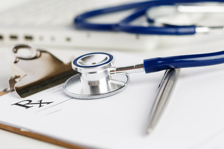 doktor: Formularz Recepta leżąc na stole z stetoskop i srebrne pióra. Koncepcja medycyny lub farmacji. Pusta forma medyczna gotowa do użycia. Medycyna narzędzia i przyrządy na stole roboczym lekarza
