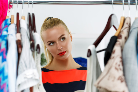 wardrobe closet: Thoughtful beautiful blonde woman standing near wardrobe rack full of clothes and choosing dress. Shopping and consumerism or stylist concept. Nothing to wear and hard to decide concept