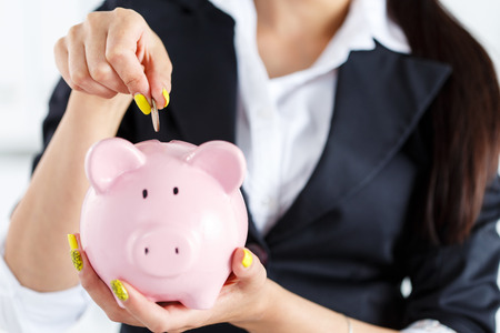 money and saving: Business woman putting pin money coins into pink piggybank slot. Budgeting expenses concept. Making savings and effective investment concept. Future needs deposit.Focus on coin Stock Photo
