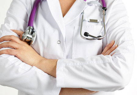 chest women: Female medicine doctor standing with hands crossed on her chest closeup. Medical help or insurance concept. Doctor is waiting for patient to examine. Physician reception concept