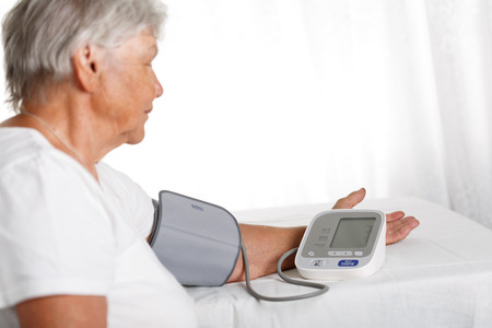 diagnosing: Elder woman measuring blood pressure with automatic manometer at home. Self health control, diagnosing and healthcare concept. Long and healthy life or medical instruments and tools retail concept