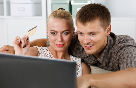 happy life: Family couple making shopping over internet looking in notebook and paying with credit card. Husband and wife buying new stuff in house. Shopping, consumerism, delivery and present concept