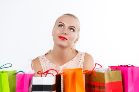 whim of fashion: Beautiful thoughtful blond woman dreaming with colored paper bags with fresh buyings and presents. Shopping, consumerism and delivery concept. Happy birthday and gifts concept