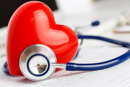 instrumental medico: Médico estetoscopio y el corazón del juguete rojo tirado en la carta de electrocardiograma de cerca. Ayuda médica, profilaxis, prevención de enfermedades o concepto de seguro. Cuidado de Cardiología, la salud, la protección y la prevención