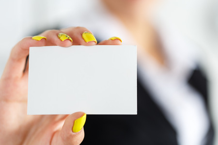 contact information: Businesswoman in suit hand holding blank calling card. Female hand showing white visiting card in camera closeup. Partners contact information exchange concept. Introducing gesture at formal meeting