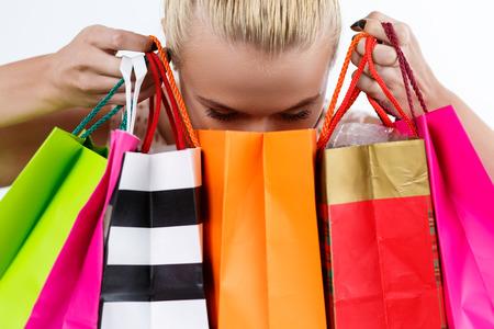 rubia: Mujer rubia inspeccionar el contenido de las bolsas de papel de colores con buyings frescas. Ir de compras, el consumismo, la entrega y el presente concepto. Concepto feliz cumpleaños y regalos