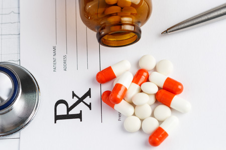 pharmacologist: Prescription form lying on table with stethoscope, pen and pile of pills fell out from jar. Medicine or pharmacy concept. Tablets and recipe.