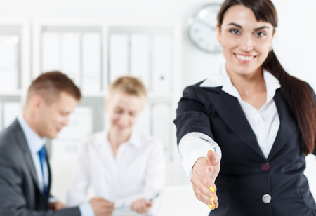 welcome symbol: Beautiful smiling business woman in suit offering hand to shake while couple employees working in background. Serious business and partnership concept. Formal greeting and welcoming gesture