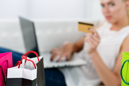 paying with credit card: Blond woman making purchasing via internet paying credit card. Focus on fresh buyings packed in colored paper bags standing in front of her. Shopping, consumerism, delivery and present concept
