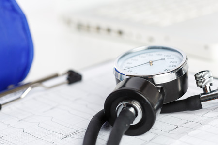 prophylaxis: Medical manometer lying on cardiogram chart closeup. Medical help, prophylaxis, disease prevention or insurance concept. Cardiology care,health, protection and prevention. Healthy life concept